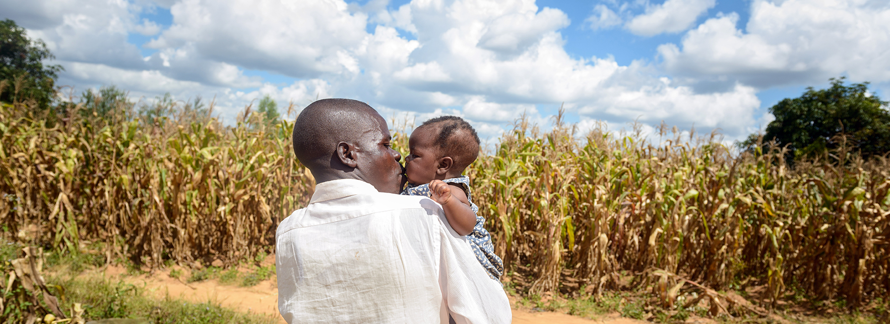 Father kisses baby daughter in Malawi.